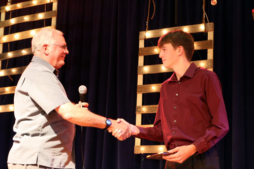 Senior Tyler Laird, right, shakes his fathers hand as he receives his award for cross country at the fall sports awards banquet, Nov. 25.